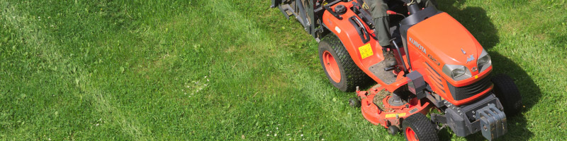 A riding lawn mower working in a field.
